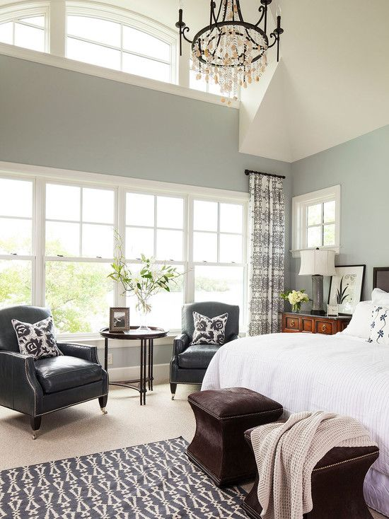 Beautifully put together master bedroom with all of the essentials: high ceilings, lots of light, a seating area, ottomans at the foot of the bed, and everything comfy.