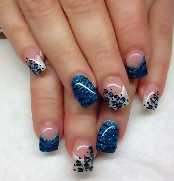 Blue themed animal print nail art design with French tips. Clear coat is used as base color with white polish for the French tips. Blue glitter nail polish is also used