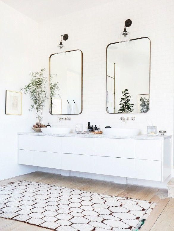 Love this all-white bathroom with brass-edged mirrors, floating modern cabinets and geometric patterned rug on the hardwood floor.
