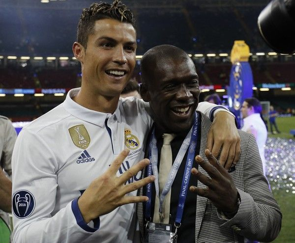 Real Madrid's Portuguese striker Cristiano Ronaldo celebrates Dutch football manager and former player Clarence Clyde Seedorf after Real Madrid won the UEFA Champions League final football match between Juventus and Real Madrid at The Principality Stadium in Cardiff, south Wales, on June 3, 2017.  / AFP PHOTO / Adrian DENNIS