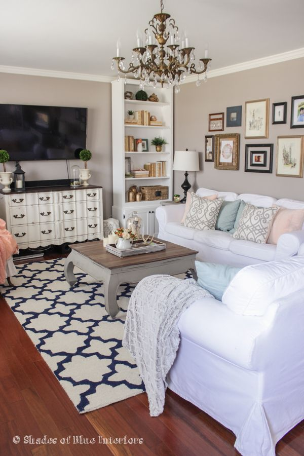 Love the white slipcovered sofas in this neutral living room eclecticallyvintage.com