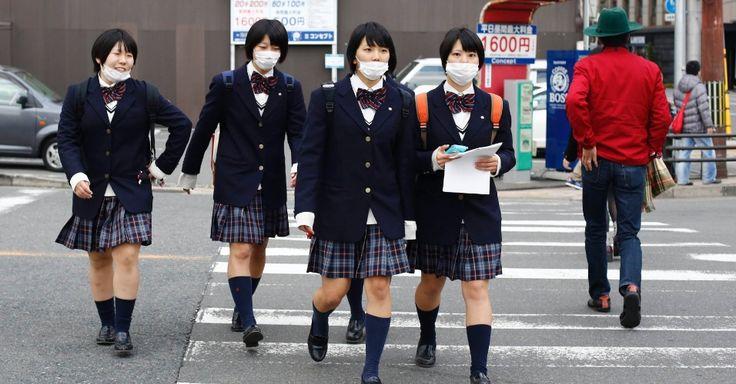 Estudantes com os rostos protegidos contra a poluição cruzam a rua na hora do almoço em Quioto, Japão.  Fotografia: Reuters / Thomas Peter.  http://educacao.uol.com.br/album/2014/03/18/educacao-pelo-mundo.htm#fotoNav=71