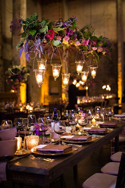"""Though it's not an option at all venues, having the opportunity to decorate upward is one Amy Zaroff of Amy Zaroff Events   Design loves. """"We hung branches, orchids, ranunculus, and roses in deep shades of purple and fuchsia over long farm tables, giving guests plenty of space to talk across the table and still enjoy the gorgeous arrangements and bask in the glow of candlelight."""""""