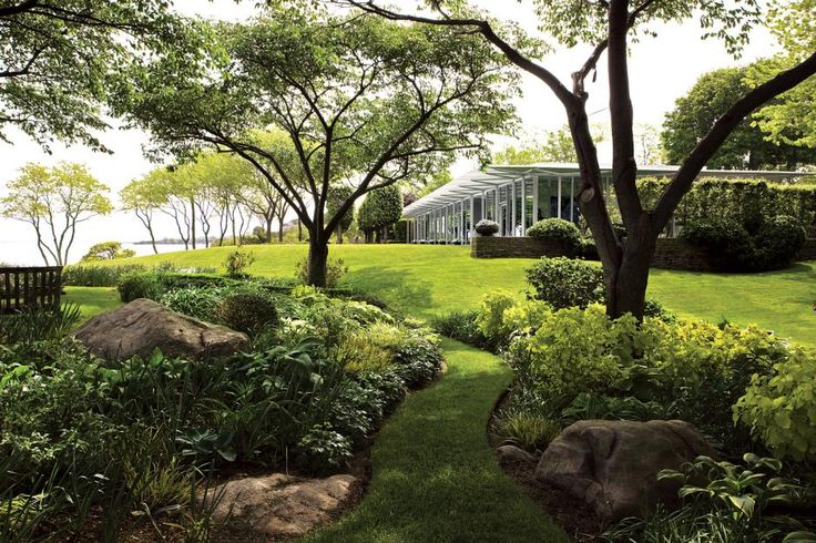 Away from the rigorous modern lines of the house, the garden's curves assert themselves in gently winding beds and paths, the snaking trunks of honey locust trees, and the swags of pruned hydrangea rolling over the perimeter wall.