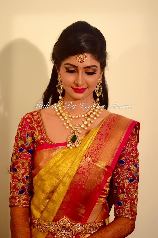 Traditional Southern Indian bride, Aishwarya wears bridal silk saree and jewellery for her reception. Makeup and hairstyle by Vejetha for Swank Studio. Pink lips. Bridal jewelry. Statement necklace. Bridal hair. Silk sari. Bridal Saree Blouse Design. Indian Bridal Makeup. Indian Bride. Gold Jewellery. Statement Blouse. Tamil bride. Telugu bride. Kannada bride. Hindu bride. Malayalee bride. Find us at https://www.facebook.com/SwankStudioBangalore