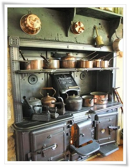 Old Victorian kitchen with a large stove and a collection of old pots, pans, and kettles.