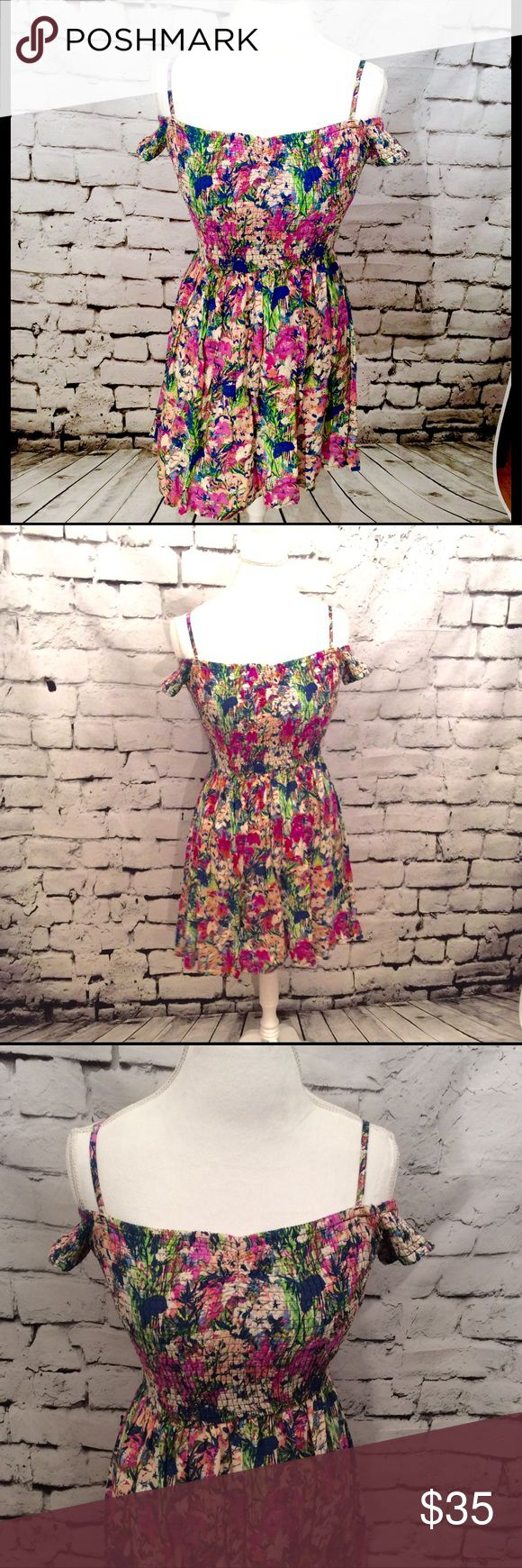 """Band of Gypsies Floral Print Off Shoulder Dress Beautiful bright colored floral print dress by Band of Gypsies. Print is pink, green, blue, and cream colors. Features stretchy smocked top and flared skirt. Features adjustable straps and short sleeves that can be worn off the shoulder. 100% rayon. Bust measures approx 27"""" unstretched, waist measures approx 26"""" unstretched and length is approx 28"""". Lots of stretch to it! Band of Gypsies Dresses"""