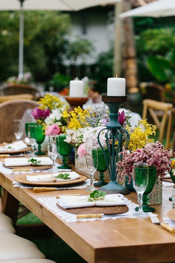 Mesa dos convidados em Casamento na Praia do Forte. Mesa em madeira, com flores coloridas, sousplat de ratán, cardápio indiviual com detalhe de ramo de folha. Talheres de bambu, taças coloridas.    Foto: Duo Borgatto  Assessoria: Indira Marrul