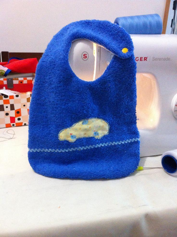 Babero de toalla azul con coche de parajitos
