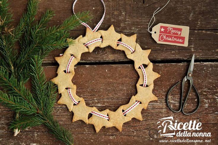 Una ghirlanda di biscotti profumati alla cannella tutta da sgranocchiare! Potete usarla come decorazione da appendere sul portone o come centrotavola per il pranzo di Natale. Non stendete la frolla molto sottile altrimenti i biscotti si spezzeranno.