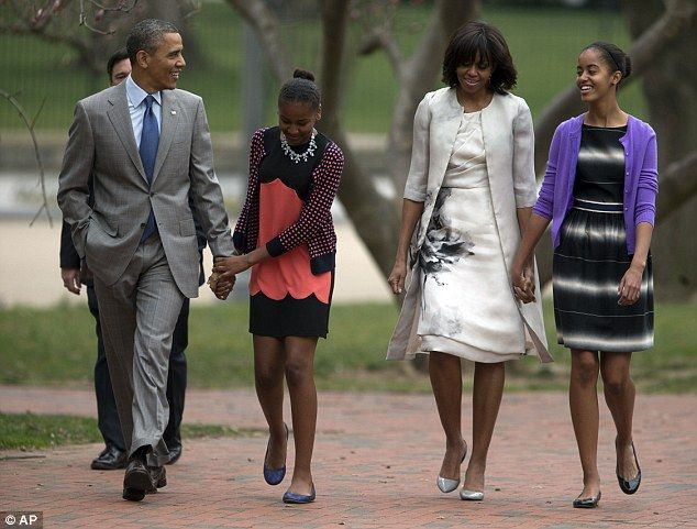 President Barack Obama and first lady Michelle Obama walk from the White House with their daughters Sasha Obama, (second from left), and Malia Obama, (right), on their way to Easter Sunday mass