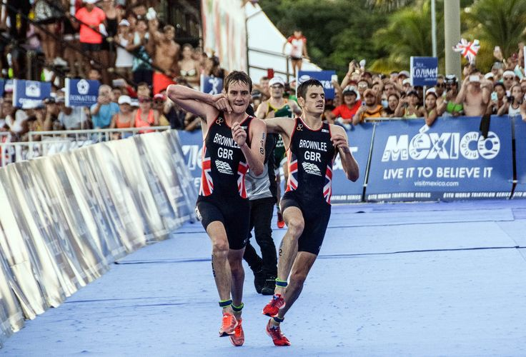 British athlete Alistair Brownlee (left) helps his exhausted brother Jonathan Brownlee to cross the finish line in second and third place during the ITU World Triathlon Championships 2016 in Cozumel, Quintana Roo, Mexico on September 18, 2016.