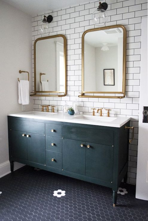 Gorgeous bathroom features accent wall clad in white subway tiles with black grout framing a black footed dual vanity topped with white quartz  framing his and her sinks paired with gold faucets under Restoration Hardware Astoria Mirrors With Trays in Antiqued Brass illuminated by glass and oil-rubbed bronze globe sconces atop a black hex tiled floor accented with white flower mosaic tiles.