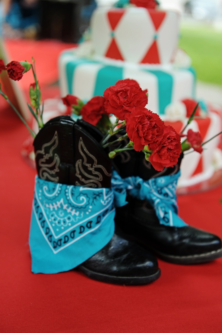 For a country themed wedding, we used children's cowboy boots with teal bandanas tied on and red carnations inside.  Every table was a different pair of boots.