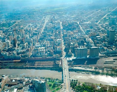 Aerial view of Melbourne, taken on 29 August 1967. The view is facing north, with the Yarra River at the southern end of the view, bisected by Princes Bridge. The Flinders Street railyards can be seen at far right, with the two multi-storey Gas and Fuel Buildings directly north of them.