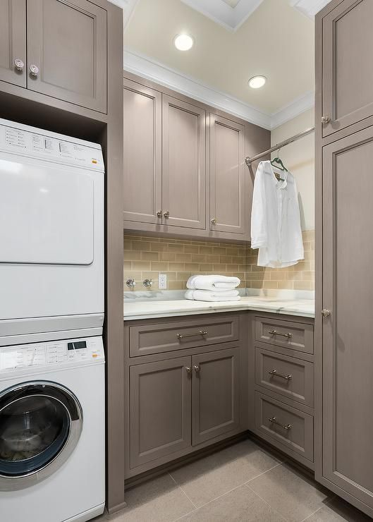 Gray laundry room features gray shaker cabinets painted Benjamin Moore River Reflections paired with statuary marble countertops and a gray glazed subway tiled backsplash.