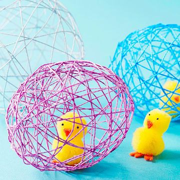 It's not hard to hatch this fun project. The steps are easy and the supplies are cheap, cheap, cheap!                 1. Make a chick by gluing together two yellow pom-poms. Glue on a felt beak and feet. Add eyes with dimensional fabric paint. Let dry. 2. Insert the chick into a prestretched balloon. Blow up the balloon until it's the size of a tennis ball. Knot the balloon and spray it with a light coating of cooking spray. 3. Cut perle cotton string into six or seven 2-foot lengths. 4…