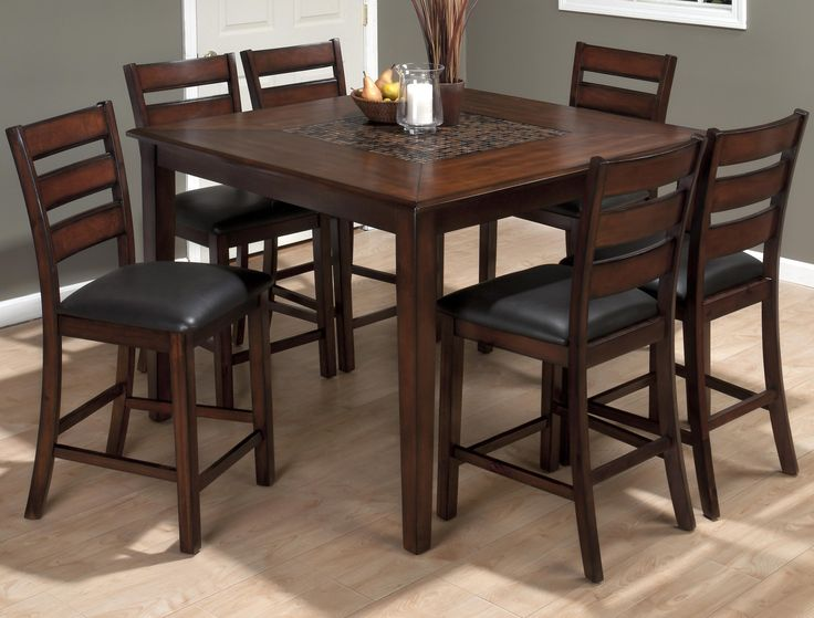 Brush up on the style elements inside your home with the casual and contemporary design that this pub height table set brings. A counter height table set with a square table and six bar stools, this set features an updated look with a mosaic inlay table and slat back chairs that take classic mission elements and turn them contemporary. The set is complete with faux leather upholstered seat cushions and a rich brown finish with charcoal toned highlights.