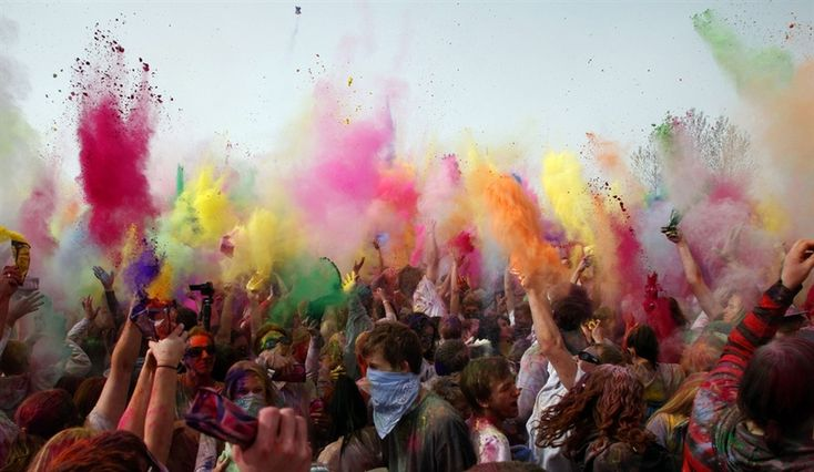 People throw colored powder during Holi, the festival of colors, at the Sri Sri Radha Krishna Temple.