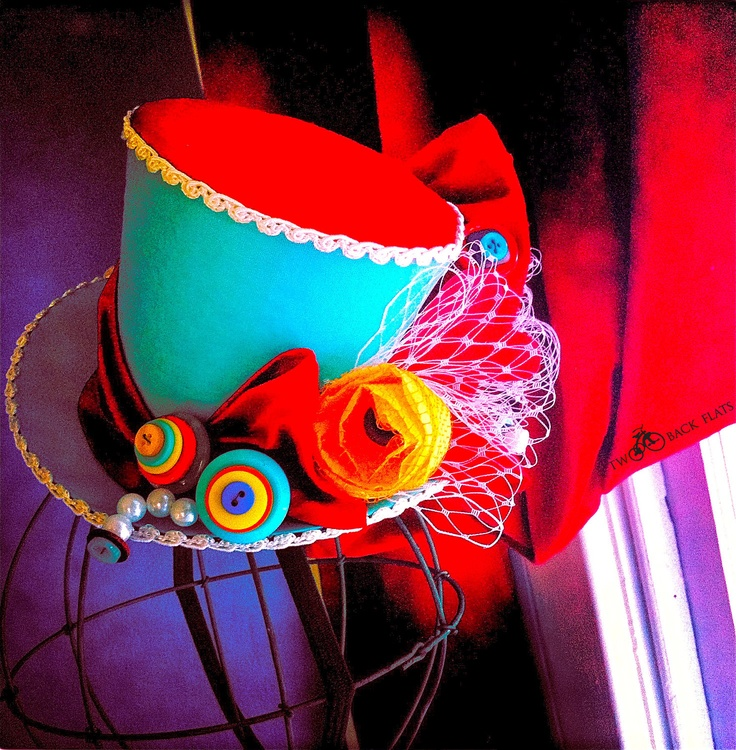 You can make a little top hat. Bright colors, buttons, fake flowers, lace netting from those onions in the kitchen. Add a bow if you must. Burning Man.