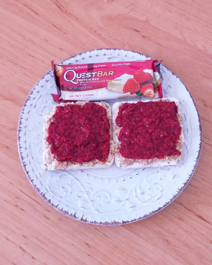 Peanut butter+homemade raspberry-chia jam on puffed rice slices and raspberry-white chocolate protein bar for breakfast.