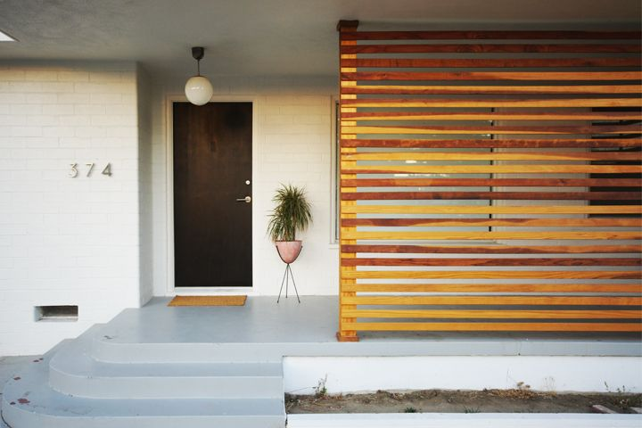 Plain 50s house glammed up with door paint, modern numbers, globe fixture, and horizontal slatted wall...