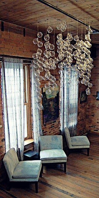 This bubble chandelier was created in a wine bar for new years eve. Easy DIY project by hanging clear ornaments from the ceiling at varying heights then spot light it using track lighting turning it into a beautiful focal point & source of light.