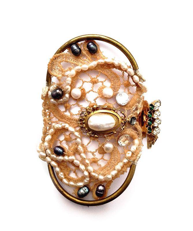 Brazalete Odecc.                                                         Precio: 89€                                                            Brazalete de encaje XXL, decorado con un intenso collage de perlas de río, un broche vintage, cristales de swarovsky y un sofisticado cierre chapado en oro con cristales checos en tonalidades verdes y blancas