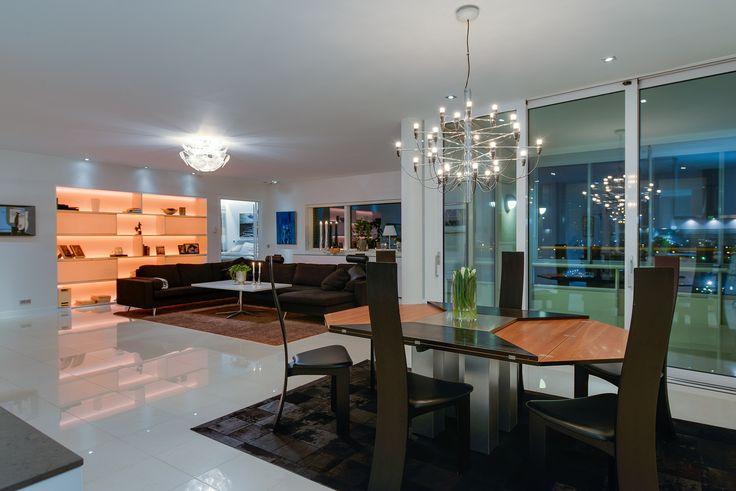 Vardagsrummet går helt i vitt och erbjuder en generös yta för både soffgrupp och större matbord. En inbyggd, egendesignad bokhylla i vitt med bakomliggande LED-belysning ger karaktär åt rummet och är både snygg att se på och praktisk. Matadorgatan 2 i Halmstad.