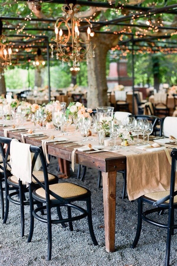 Beautiful outdoor setting with linen table runner, small scattered centerpieces and beautiful glasses.
