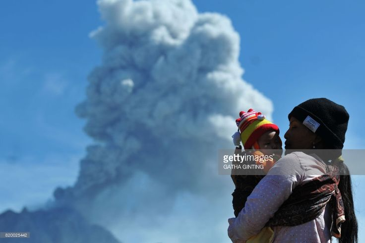TOPSHOT - A woman carries her child as she watches Mount Sinabung volcano spewing thick volcanic ash, as seen from Karo on July 21, 2017. Sinabung roared back to life in 2010 for the first time in 400 years, after another period of inactivity it erupted once more in 2013, and has remained highly active since. /