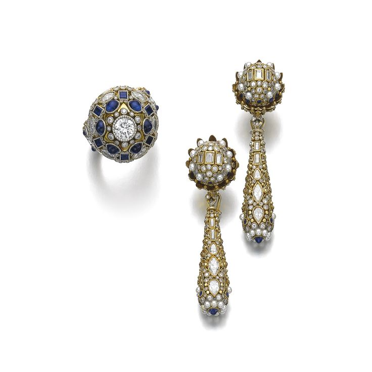 Gem set and diamond demi-parure, Elmar Seidler, first half of the 20th century. Comprising: a pair of earrings and a ring decorated on the front and back with intricate metal work, millegrain-set with variously cut sapphires and diamonds, the earrings accented with seed pearls, the ring set with a cabochon pink sapphire on the back of the shank.