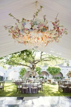 Beautiful floral chandelier. 15 Gorgeous Ways to Decorate Your Wedding Tent via Brit + Co