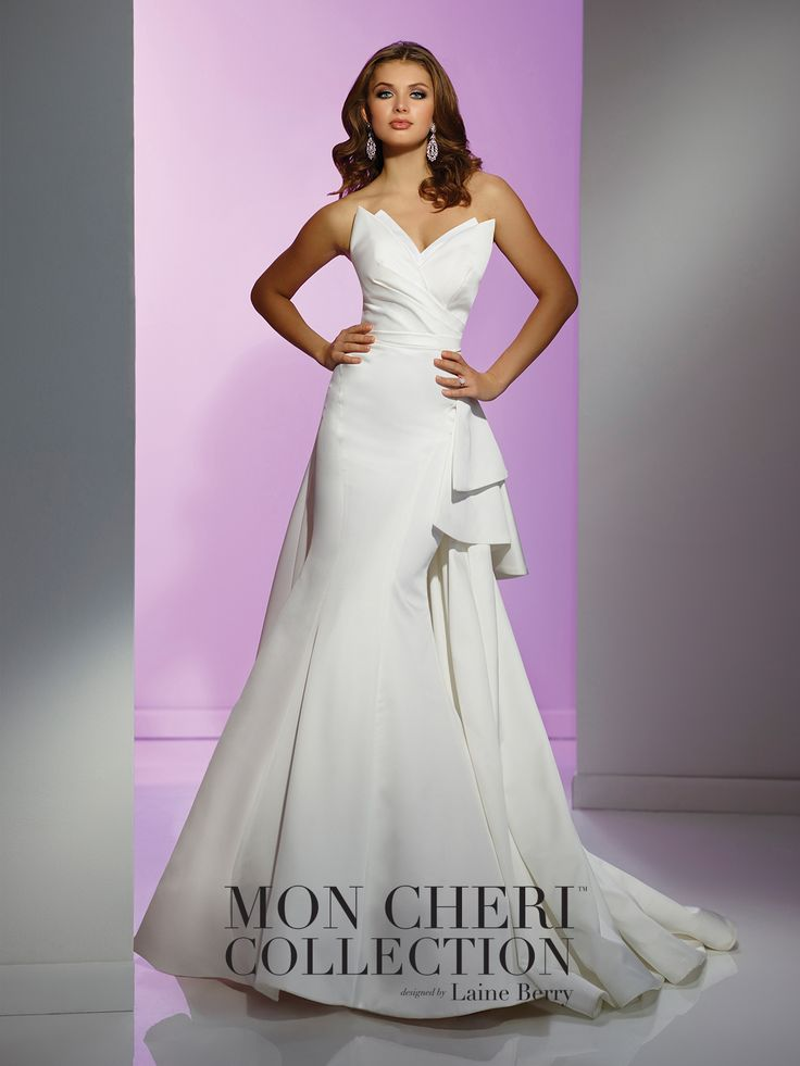 Strapless silk satin fit and flare wedding gown features a uniquely sculpted neckline, side draped waistline, two-tiered side ruffle accent continues around to back, architecturally seamed skirt with sweep train, detachable halter and spaghetti straps included. Custom colors are also available. Sizes: 0 – 16 Colors: Ivory, Red/Magenta