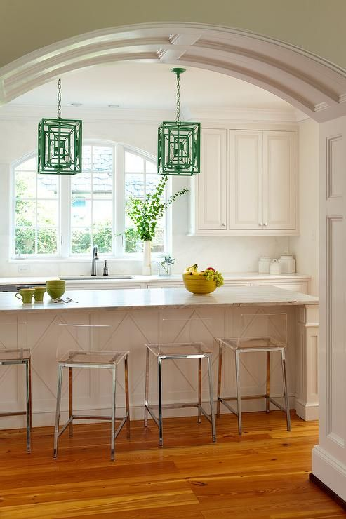 An arched doorway opens to a kitchen filled with a long white center island with diamond pattern trim moldings topped with honed marble lined with CB2 Vapor Bar Stools illuminated by green lanterns, Stray Dog Designs Jay Chandeliers.