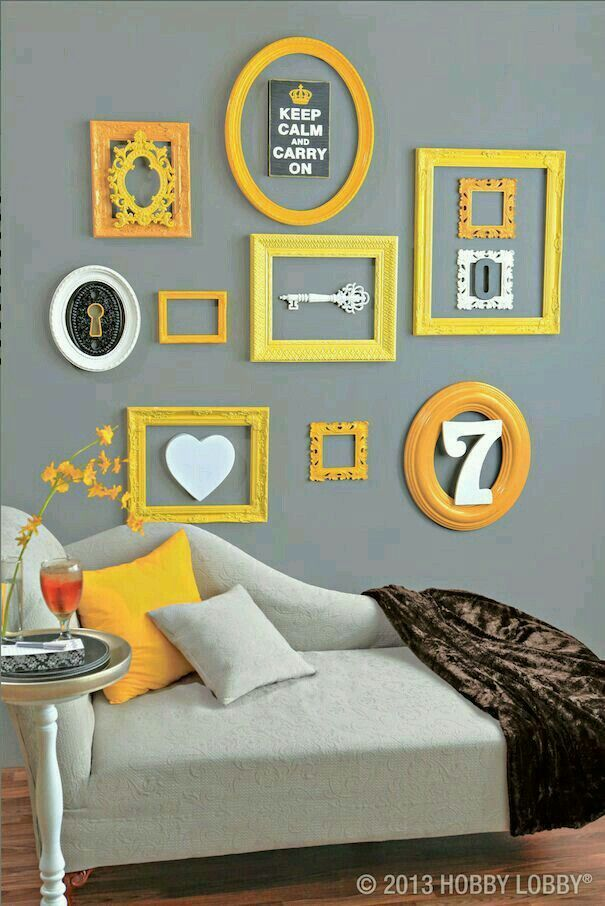 Molduras e posters amarelos e pretos na parede da cama
