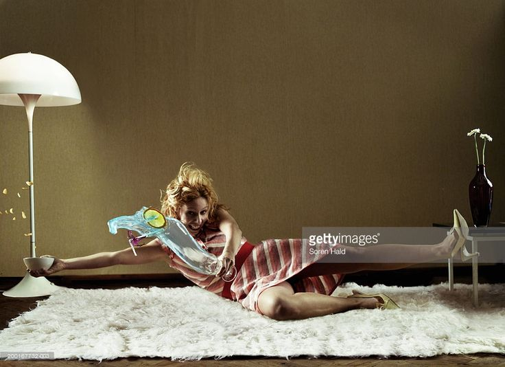 Stock Photo : Young woman falling on rug, spilling drink and crisps