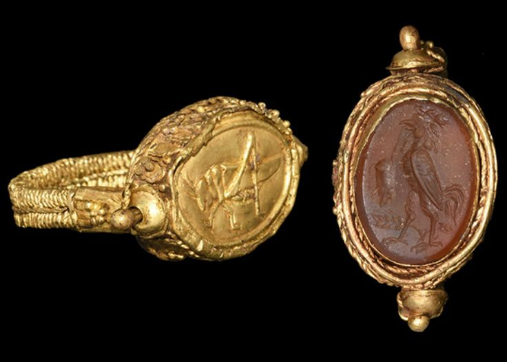 Greek Olbian Gold Seal Ring, 7th-5th Century BCWith a locust motif; inset carnelian panel with intaglio motif of a cockerel standing on an ear of wheat with a mouse in its beak. The ring was used as a seal matrix for sealing amphorae of wheat (hence...