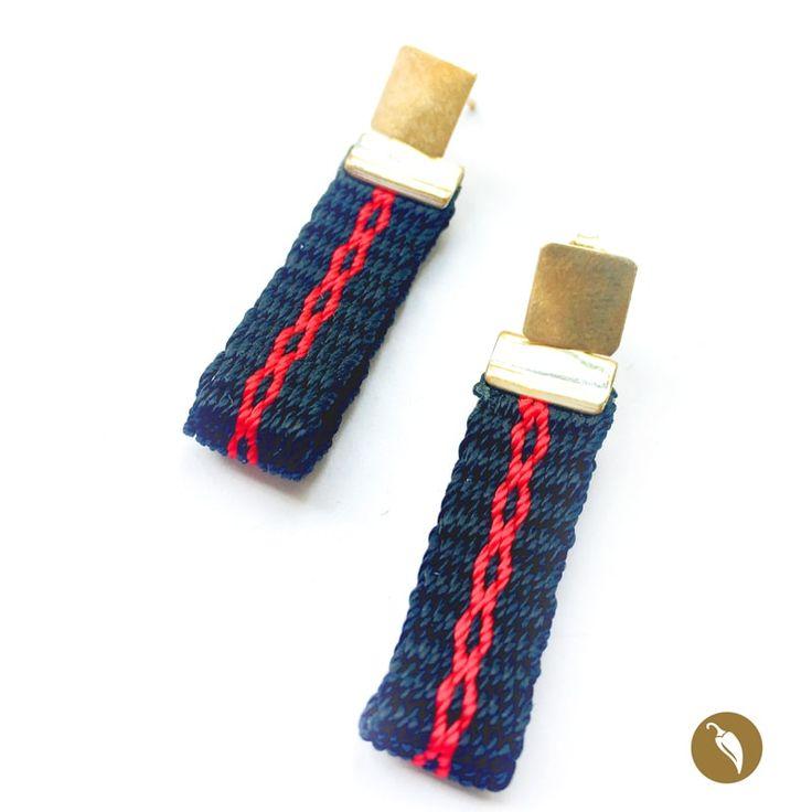 """Arosdonde el protagonista absoluto es una pequeña pieza tejida a telar. Gabriela Casteránrescata estatécnica para honrar nuestros orígenes. De un tope metálico se suspende la pieza a telar.El brillo del metal se contrapone a la calidez de las fibras de tonos oscuros en los que sedistingue un diseño central. Estos aros son parte de la colecciónNahuenque alude al fonema Newen que significa """"Energía""""enMapudungún. El arte textil mapuche data de tiempos precolombinos y…"""