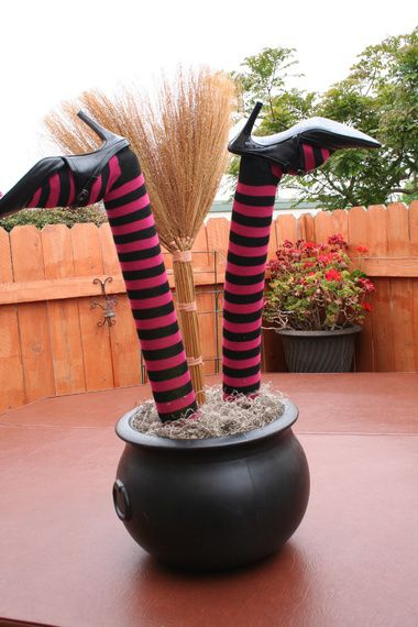 """Home made Crashed Witch Prop. """"Got the Union Products cauldron at a rummage sale for 50 cents, dollar store knee socks $1 and spanish moss $1, yard sale shoes .50, broom $1.50. Used an old pool noodle for legs and some scrap foam inside the cauldron. Also used some dollar store bamboo sticks $1 to stick inside the pool noodles and into the foam in the cauldron. Threw some rocks into the bottom of the cauldren before the foam, to stabilize the whole thing. Total cost = $5.50,"""