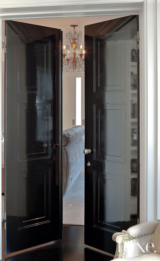 A vintage chandelier from Boxwood is glimpsed beyond the master suite's glossy black doors.