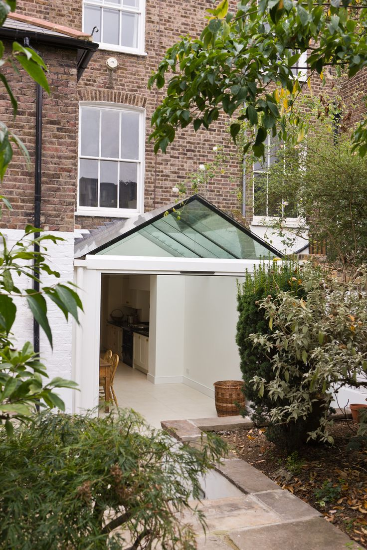 Side Infill Dining Room Extension With A Frameless Glass Roof And Beams