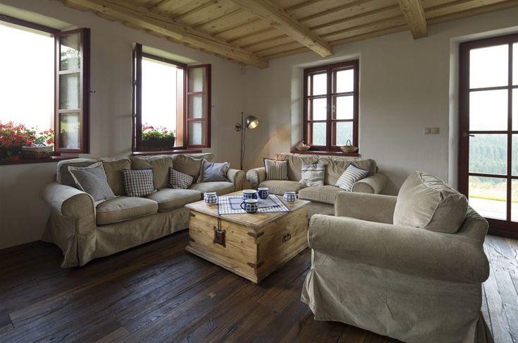 """Masivní dřevěná podlaha a čalouněný nábytek z IKEA si dobře rozumějí s českým """"venkovským"""" textilem a keramikou."""