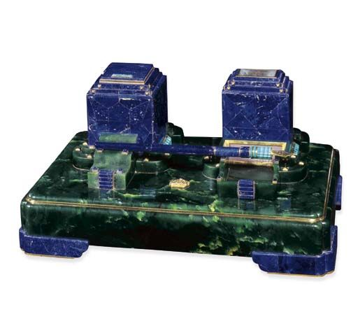 AN IMPORTANT ART DECO NEPHRITE, LAPIS LAZULI AND SAPPHIRE DESK SET, BY CARTIER The rectangular nephrite base surmounted by a square lapis lazuli inkwell, the silver inkpot with white enamel interior and a rectangular cigarette holder, which has a removable receptacle at its base containing a strike area and space for matches; there is in addition a lapis lazuli and malachite fountain pen which rests on steps with cabochon sapphire detail, crown in centre of base, circa 1928, Signed Cartier