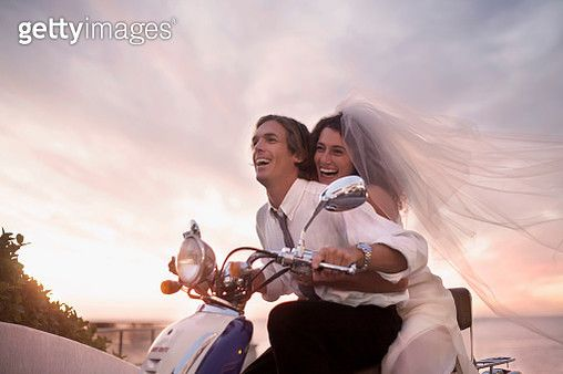 Bride and groom riding motorcycle on beach against sunset - gettyimageskorea