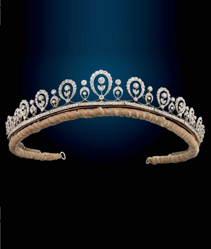 An Edwardian platinum diamond tiara. Of garland design, comprising a series of old and single-cut diamond graduated foliate and loop motifs, each with principal old-cut diamond collet and surmount, to the single-cut diamond bar links and base metal frame. With fitted P.G Dodd & Son case. #Edwardian