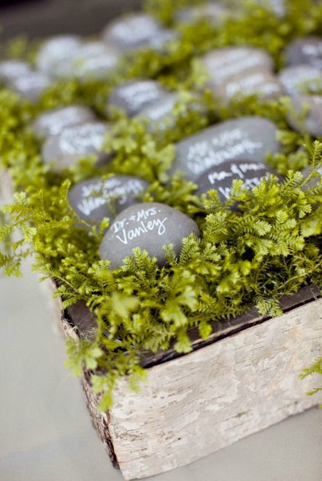 Rocks nestled in birch boxes filled with lush greenery makes for an enchanting escort card display