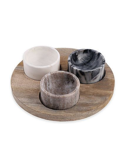 Three small but mighty marble bowls (each is approximately two inches in diameter) are nestled atop a natural wooden base for a piece that will be useful year round and at every occasion. Use it for bar snacks during cocktail hour, condiments at a grill out, spices at a formal dinner party, or sundae toppings at an ice-cream party.