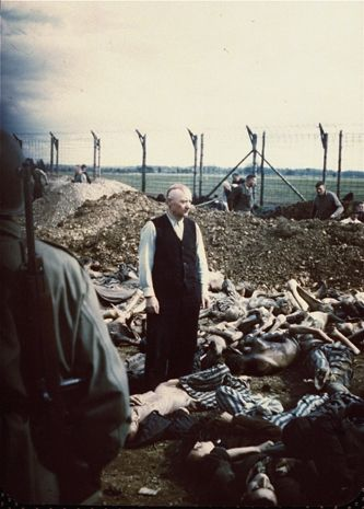 SS officer Eichelsdoerfer, the commandant of Kaufering IV, a sub-camp of Dachau, stands in civilian clothes amidst the corpses of prisoners killed in his camp. A burial party of Germans conscripted from the surrounding area works in the background, April 27, 1945 - April 30, 1945. Eichelsdoerfer was later convicted during the The Dachau Trials, held on the grounds of the camp after liberation, and was executed May 29, 1946.