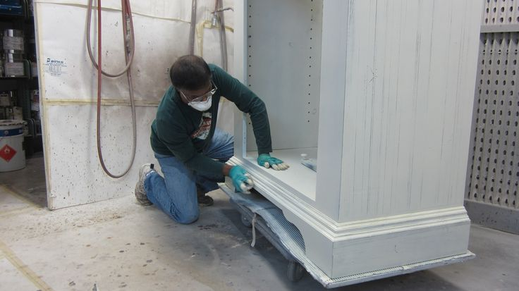 Distressing the paint to show some of the black through by AM Furniture Finishing.